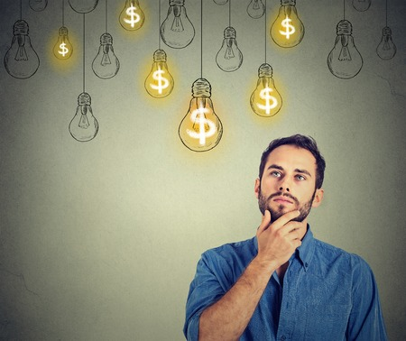 Portrait thinking handsome young man looking up at many dollar idea light bulbs above head Stock Photo