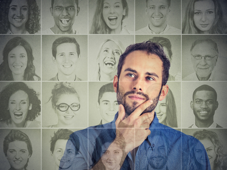Portrait of a handsome young man thinking looking up at a group of multicultural happy people Stock Photo