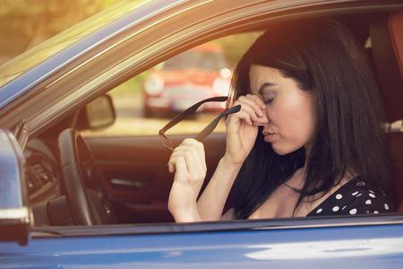 De bedrijfsvrouw die hoofdpijn hebben die haar glazen opstijgt moet een einde na het drijven van auto in opstopping op spitsuur maken. Uitgeput, overwerkt chauffeursconcept. Stockfoto