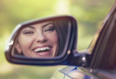Happy young woman driver looking in car side view mirror, making sure lane is free before making a turn. Positive human face expression emotions. Safe trip driving concept