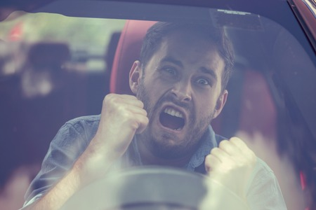Windshield view of an angry driver man. Negative human emotions face expression