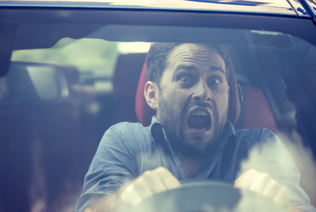 scarry: Young man driving a car shocked about to have traffic accident, windshield view