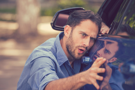 Young worried funny looking man obsessing about cleanliness of his new car on a summer day. Car care and protection concept