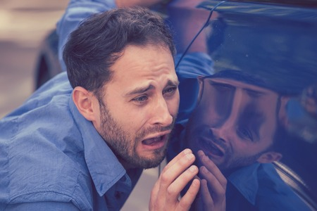 Frustrated upset young man looking at scratches and dents on his car outdoors Stock Photo