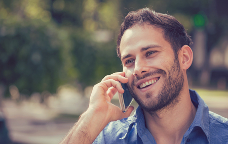 outdoor outside: Headshot of a man talking on mobile phone. Casual urban professional using smartphone smiling happy standing outside on a street . Outdoor portrait of modern guy with cellphone