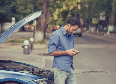 motor cars: Upset young man calling texting roadside assistance after breaking down