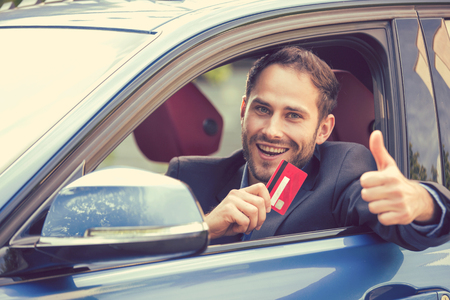 Happy smiling man sitting inside his new car showing credit card giving thumbs up. Personal transportation auto purchase concept Stockfoto