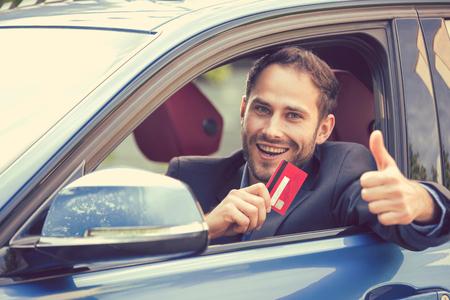 Happy lachende man zit in zijn nieuwe auto met credit card geven duimen omhoog. Persoonlijk vervoer auto aankoopconcept