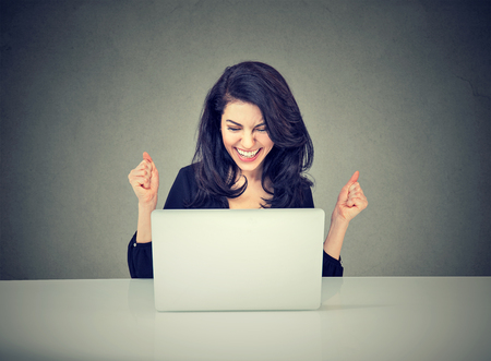 Portrait of a young businesswoman sitting with her laptop in the office celebrating success