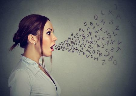 Vrouw die met alfabetbrieven spreekt die uit haar mond komen.
