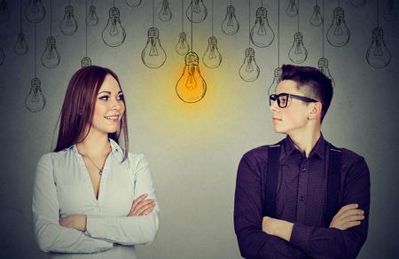 Cognitieve vaardigheden bekwaamheidsconcept, mannelijk versus vrouwelijk. Jonge man en vrouw die heldere gloeilamp bekijken elkaar geïsoleerd op grijze muurachtergrond