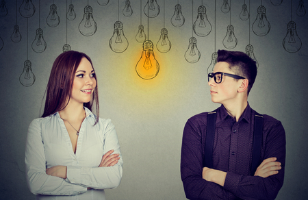 Cognitive skills ability concept, male vs female. Young man and woman looking at bright light bulb each other isolated on gray wall background