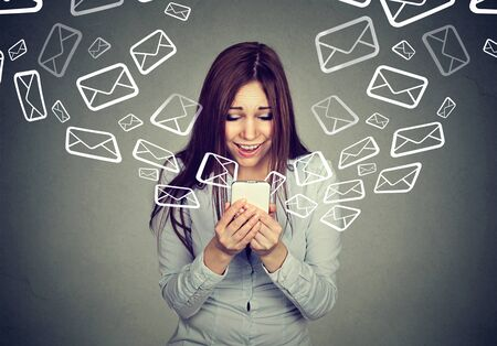 unanswered: Surprised young woman busy sending receiving many messages emails on her smart phone isolated on gray background. Telecommunications, internet, data plan concept Stock Photo