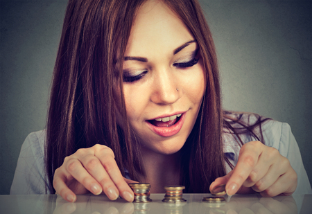 Young woman counting money stacking up coins Imagens