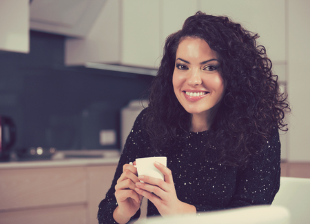 cafe colombiano: woman drinking coffee in the morning at home in the kitchen