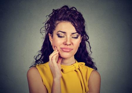 molesto: Mujer con dientes sensibles dolor corona problema a punto de llorar de dolor tocar la boca exterior con la mano aislado fondo gris. Foto de archivo