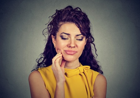 Woman with sensitive tooth ache crown problem about to cry from pain touching outside mouth with hand isolated gray background.