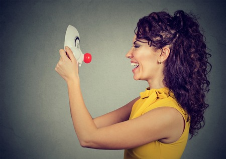 Laughing woman looking at clown mask isolated on gray wall background