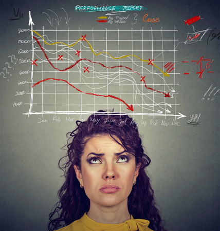 Worried woman looking at financial charts going down. Investment risk concept