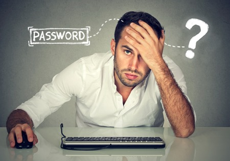 Desperate young man trying to log into his computer forgot password Banco de Imagens