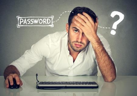 Verzweifelte junge Mann, der versucht einzuloggen in seinen Computer Passwort vergessen haben, Standard-Bild - 75950984