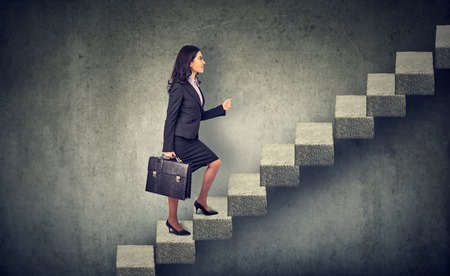 graduation suit: Businesswoman with briefcase stepping up a stairway career ladder