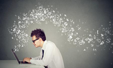 若い男が離れて飛んでラップトップ コンピューターのアルファベットで入力します。 写真素材
