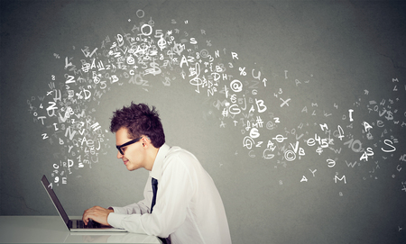Young man typing on laptop computer alphabet letters flying away