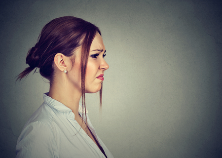 Disgusted annoyed young woman on gray background