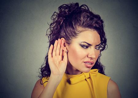 Nieuwsgierige ongerust gemaakte vrouw met hand aan oor die zorgvuldig aan roddelgesprek luisteren die op grijze achtergrond wordt geïsoleerd
