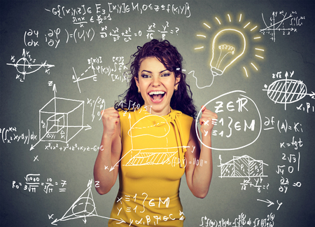 admitted: smart excited woman student with bright idea light bulb and high school maths and science formulas on blackboard background  Stock Photo
