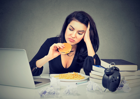 Sedentaire levensstijl en junk food-concept. Vermoeide beklemtoonde vrouwenzitting bij haar bureau die hamburger en frieten eten Stockfoto