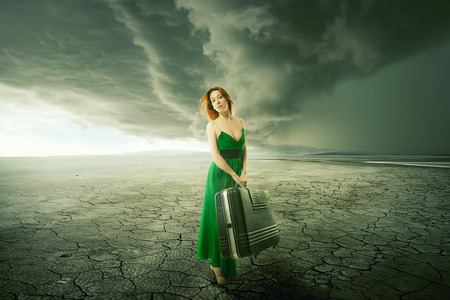 Beautiful woman in green dress with suitcase standing alone in the middle of the desert with mountains background