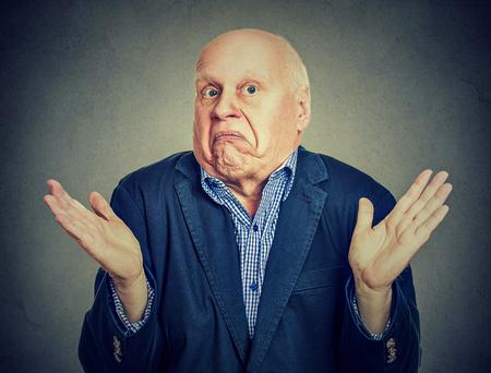 El hombre confundido mayor está encogiéndose de hombros