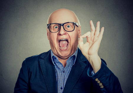 Portrait of a happy senior man showing ok sign isolated on gray wall background