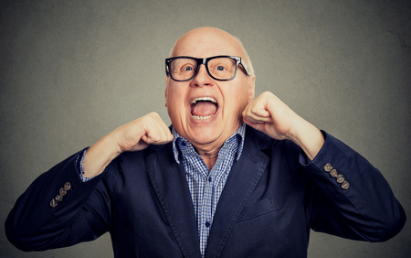 Portrait of happy laughing senior old man with hands up isolated on gray background Stock Photo