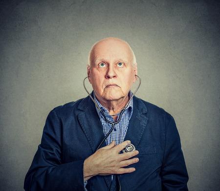 Hogere mens die aan zijn die hart met stethoscoop luistert op grijze achtergrond wordt geïsoleerd