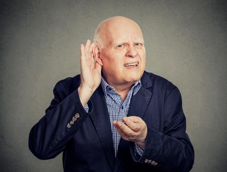 Senior man, hard of hearing, placing hand on ear asking someone to speak up