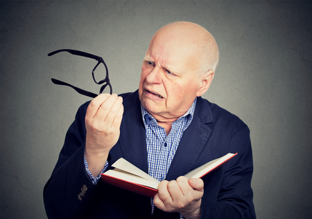 Closeup elderly, mature man holding book, glasses having eyesight problems unable to read isolated on gray background. Age related health changes Stockfoto