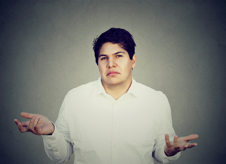 don't care: Portrait of unsure confused man shrugging shoulders isolated on gray background