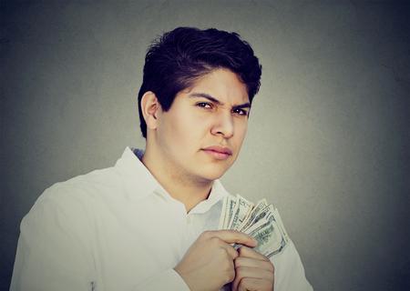 scrooge: Greedy suspicious man holding money dollar bills in hand Stock Photo