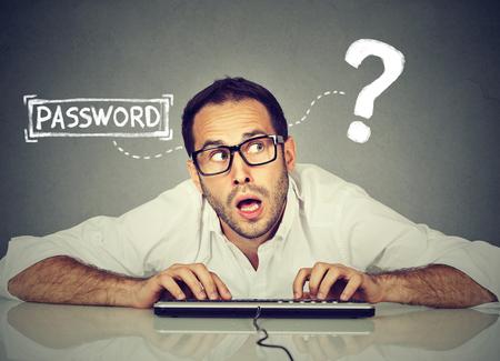男は、自分のコンピューターにログインしようとすると、キーボードで入力するパスワードを忘れてしまった 写真素材
