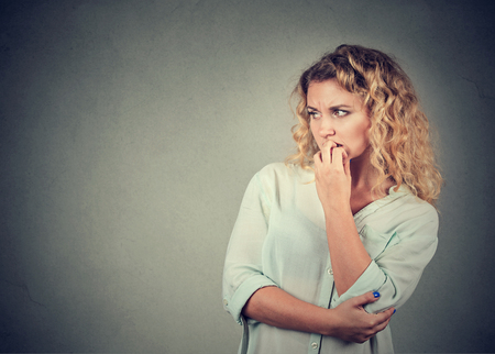 doomed: Portrait anxious woman biting her fingernails craving for something isolated on gray background. Negative human emotions