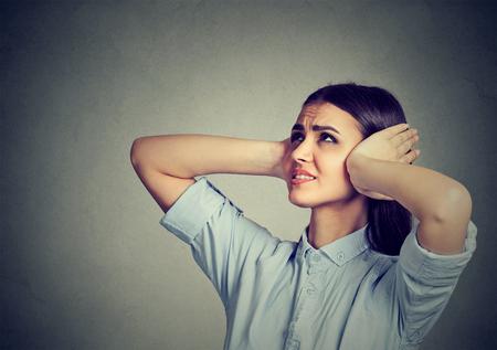 Mujer frustrada tensionada que cubre sus oídos con las manos. Foto de archivo