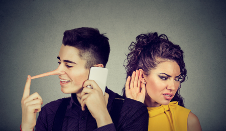 disloyal: Curious worried woman secretly listening to a happy man liar talking on mobile phone with his lover isolated on gray wall background Stock Photo