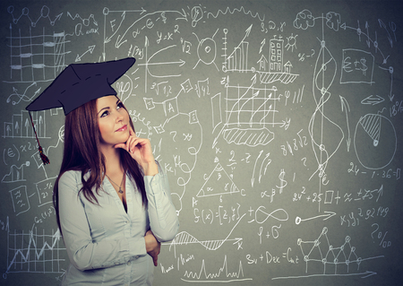 Young woman in graduation cap thinking about education, work life balance planning future standing by info graphics blackboard background
