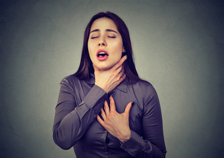 Young woman having asthma attack or choking can't breath suffering from respiration problems isolated on gray background