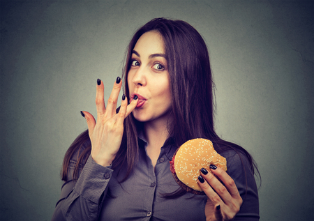 meat lover: Fast food is my favorite. Young woman eating a hamburger enjoying the taste  Stock Photo