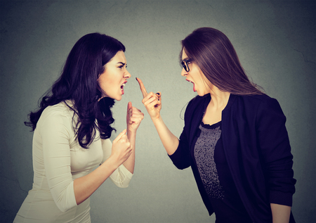Fight. Two women screaming at each other on gray wall background