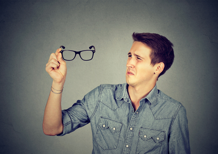 near sighted: Man with glasses having eyesight problems isolated on gray background.